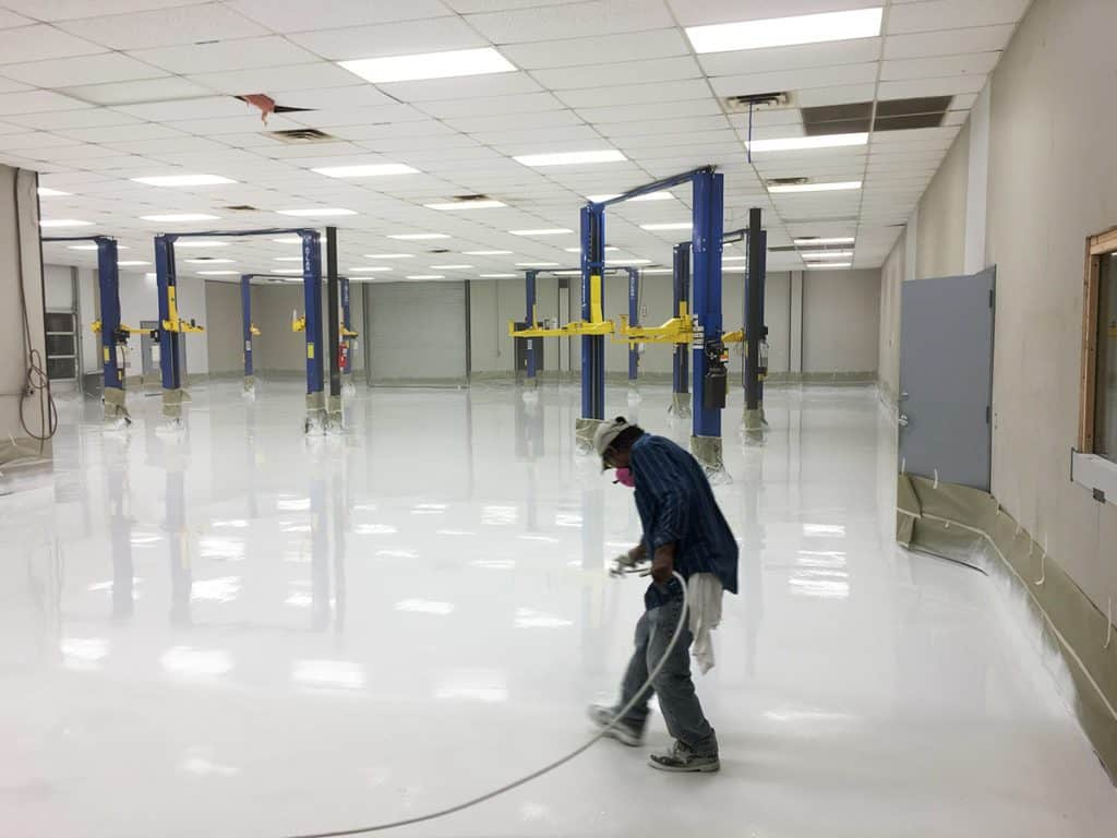 A worker is spraying white epoxy on a big commercial floor to finish epoxy flooring