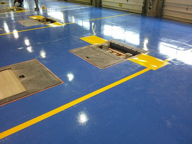 Beautiful yellow epoxy striping installed in a commercial car garage