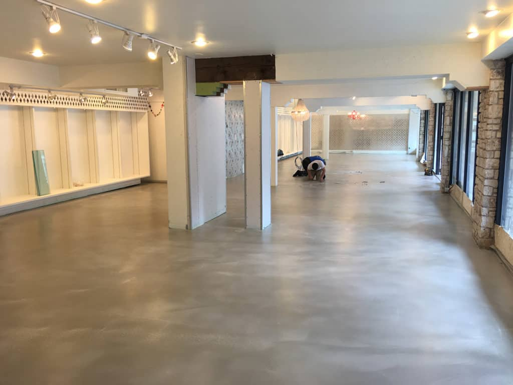 a worker is working to install concrete epoxy caoting of a retail floor
