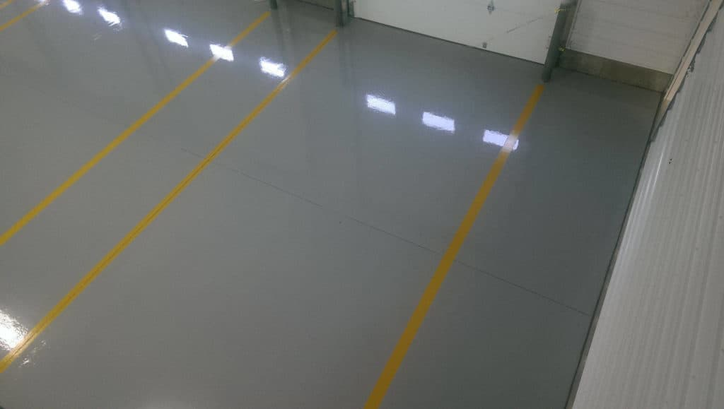 Yellow striped reflactive epoxy coated garage floor of a commercial space