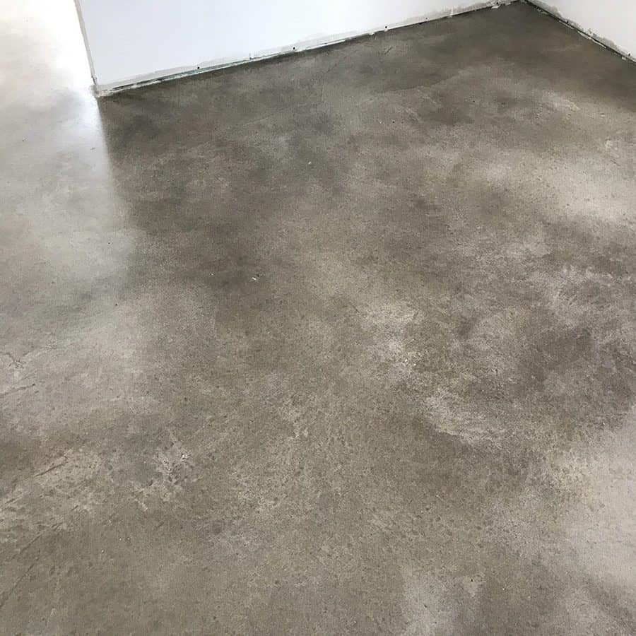 Grey stained concrete epoxy installed on a square floor
